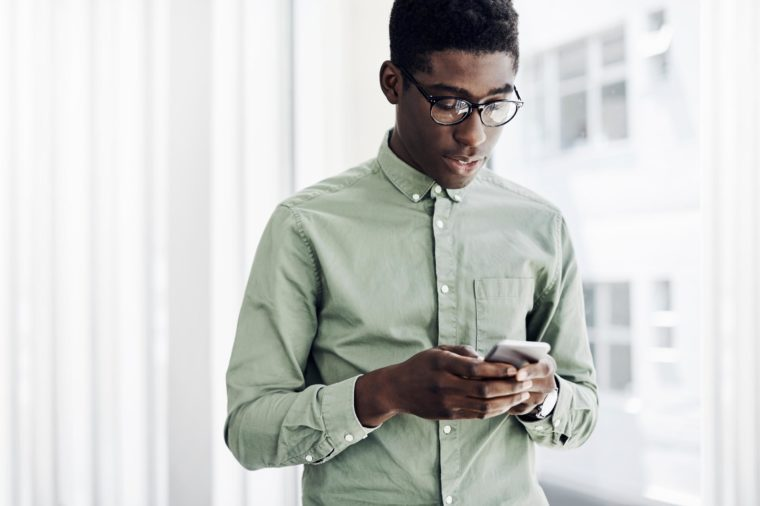 young man texting near an open window