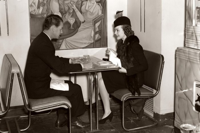 1940s Smiling Young Couple Man Woman Sitting Together On Chrome Art Deco Style Table And Chair Furniture In Modern Cafe