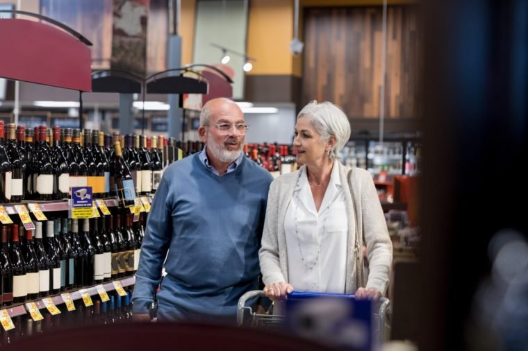 Mature Caucasian couple shop for red wine in grocery store.