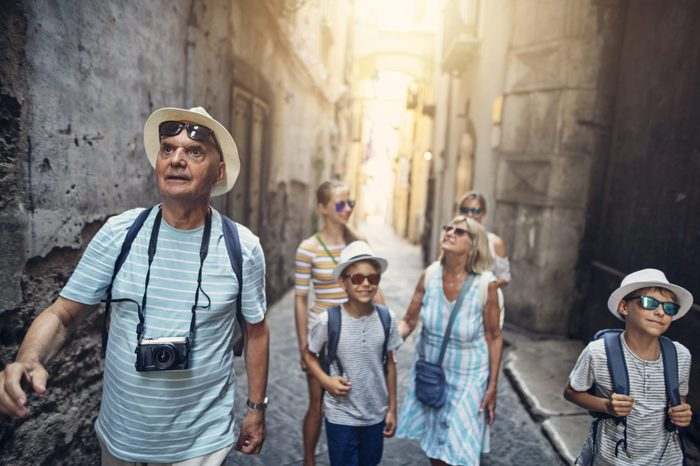 Multi generation family enjoying summer vacations. The family is walking in the narrow streets of a beautiful Italian town.