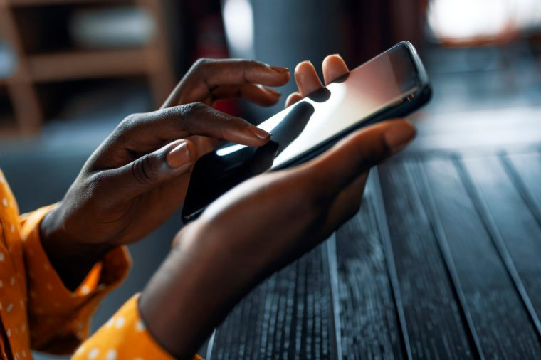 Close up of a young woman's hand typing text message on her smartphone. African young woman is typing on touch screen mobile phone. Close up of female hand texting a message phone indoor.
