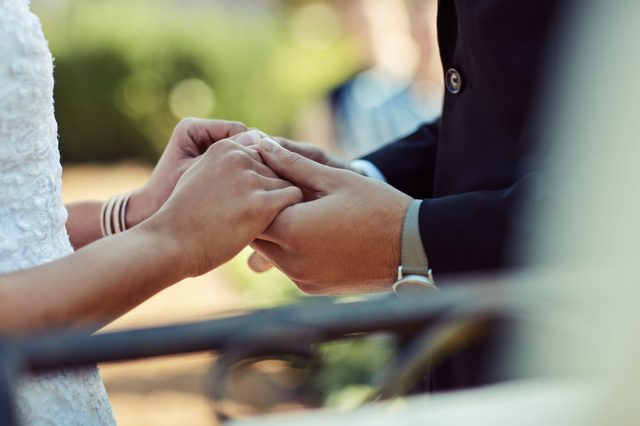 Cropped shot of a couple holding hands on their wedding day