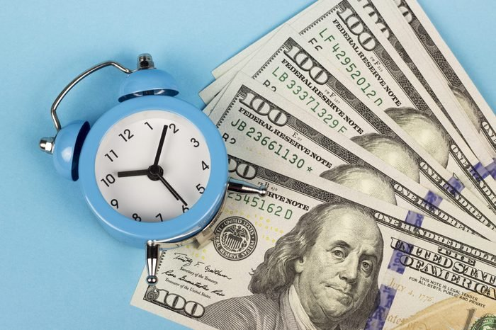 money and alarm clock on a blue background