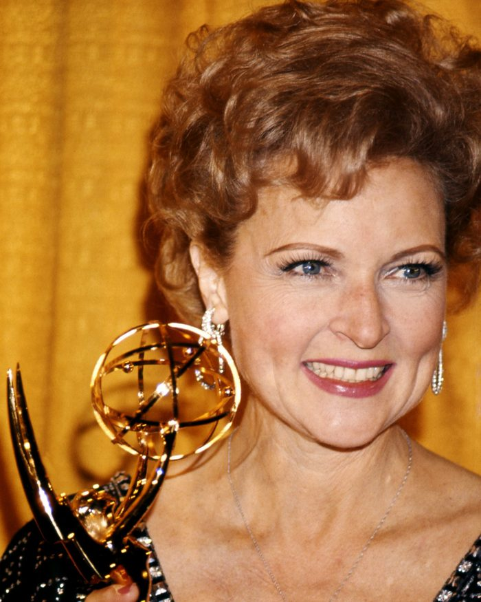 Betty White, US actress, smiling as she holds an Emmy Award, against a yellow background, USA, circa 1975.