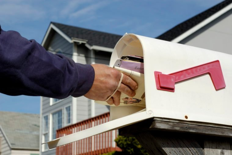 Mailman's arm inserting a bundle of mail into a mailbox. Partially obscured suburban home in background. Horizontal orientation.