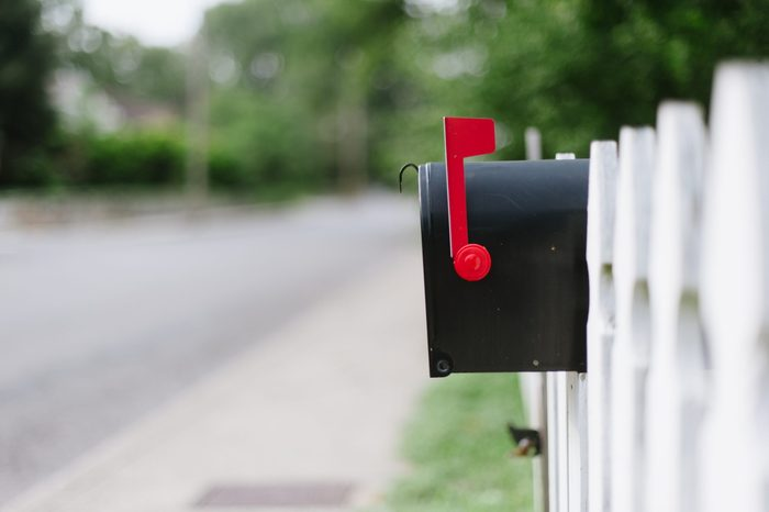 Mailbox on white fence.