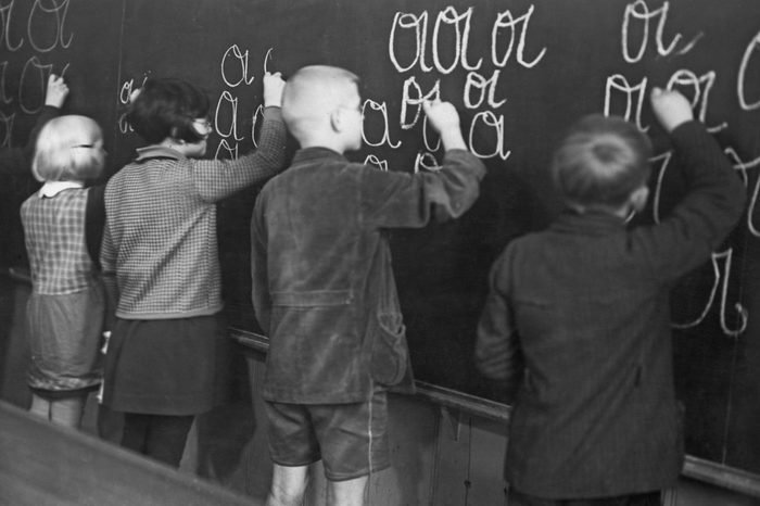 children doing writing exercises on a chalkboard in school. circa 1950
