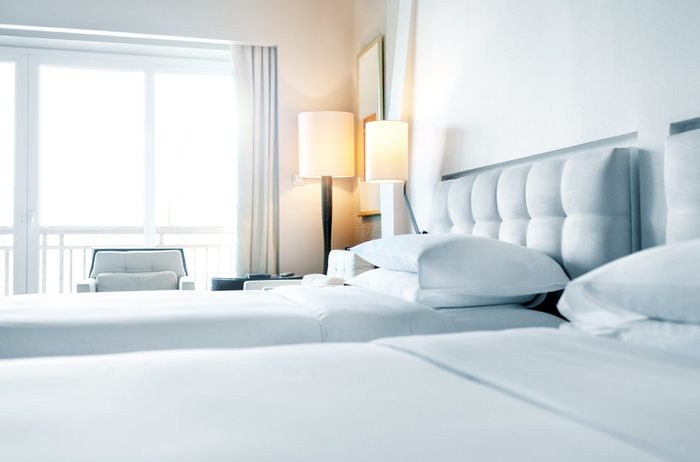 made beds in a simple white hotel room