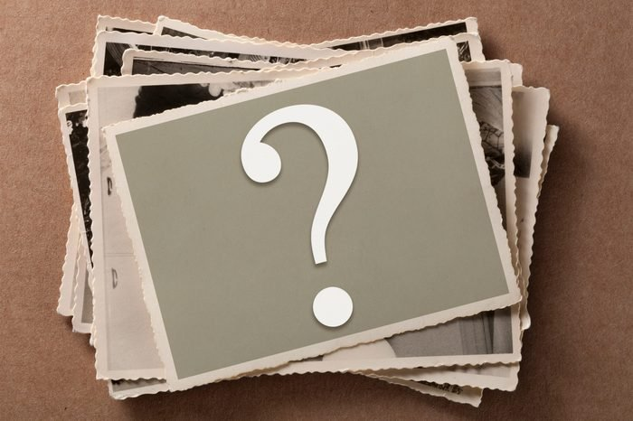 Pile of old photographs with question mark on top