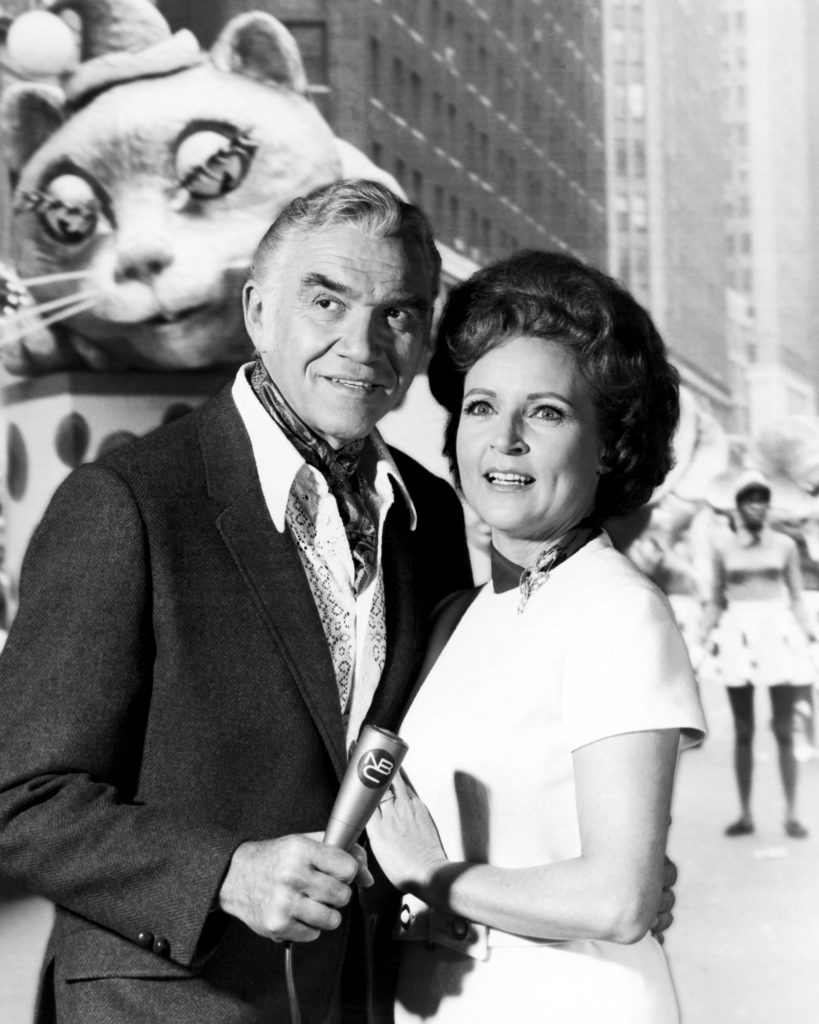 Canadian actor Lorne Greene (1915 - 1987) and American actress Betty White posing for a publicity still, in front of a back projection of a Macy's Thanksgiving Parade, 1969.