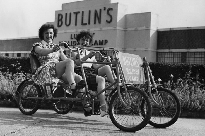 Two holidaymakers riding a bicycle for two at Butlin's Holiday Camp in Clacton