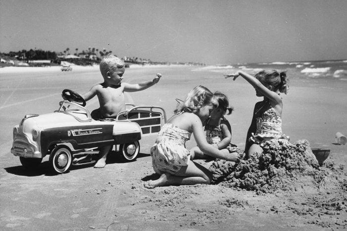 circa 1960: A young boy trying to impress three girls in his pedal car on Daytona Beach, Florida