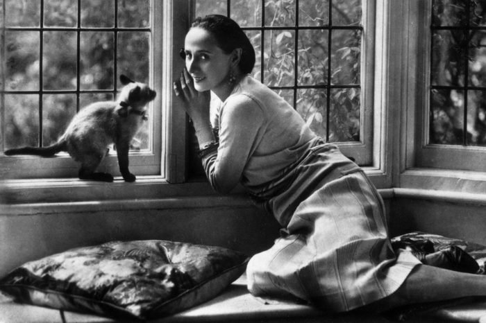 circa 1920: Russian ballet dancer Anna Pavlova (1885 - 1931) relaxing at home with her pet cat