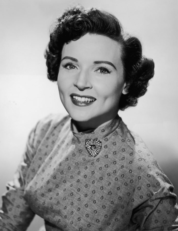circa 1955: Promotional studio portrait of American actor Betty White smiling and wearing a patterned dress with a heart-shaped brooch.
