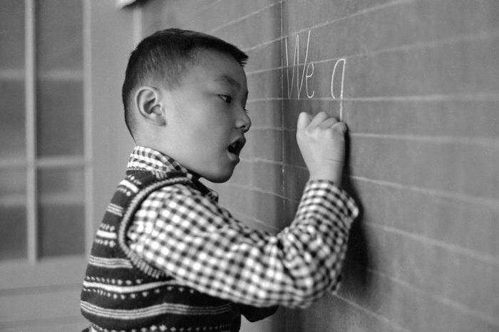 young boy writing on a chalkboard circa 1955
