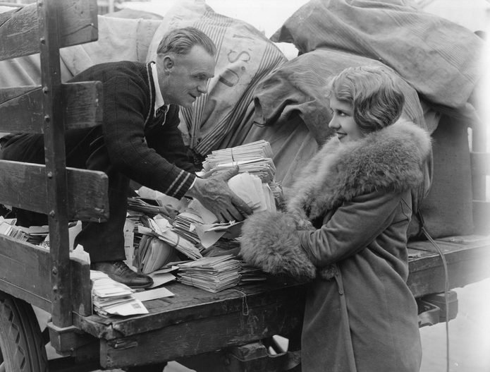 1925: A postman employed by the US mail hands a woman a pile of letters from the back of his lorry.
