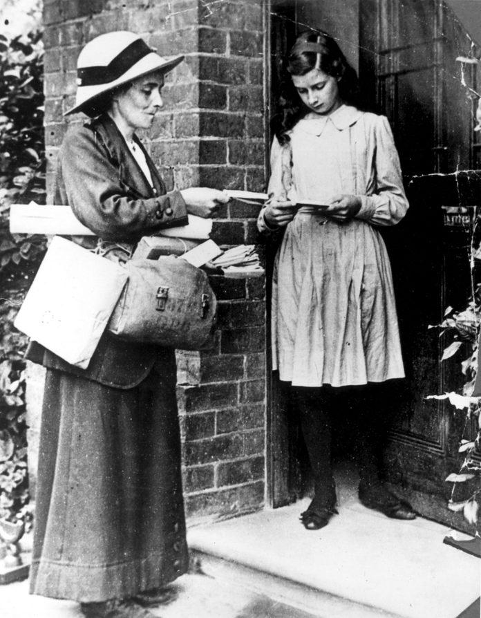 circa 1917: A post woman delivering post.