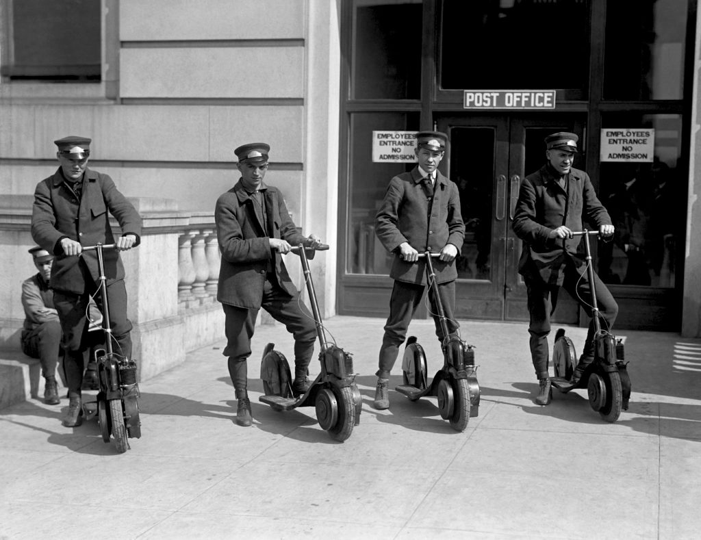 Four special delivery postmen for the US Postal Service try out new scooters, mid 1910s.