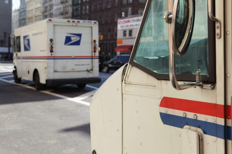 two usps trucks parked on the street