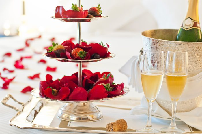 Strawberries and champagne on a hotel bed