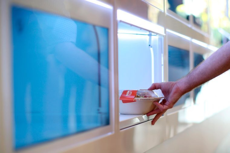a hand reaches into an automated cubbie to get his food