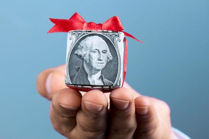 hand holding dollar bill folded like a gift