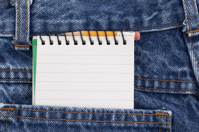 Blank lined notebook and a small pencil in the back pocket of denim jeans.
