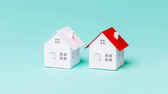 two white paper houses, one with a pink roof and one with a red roof, on aqua background