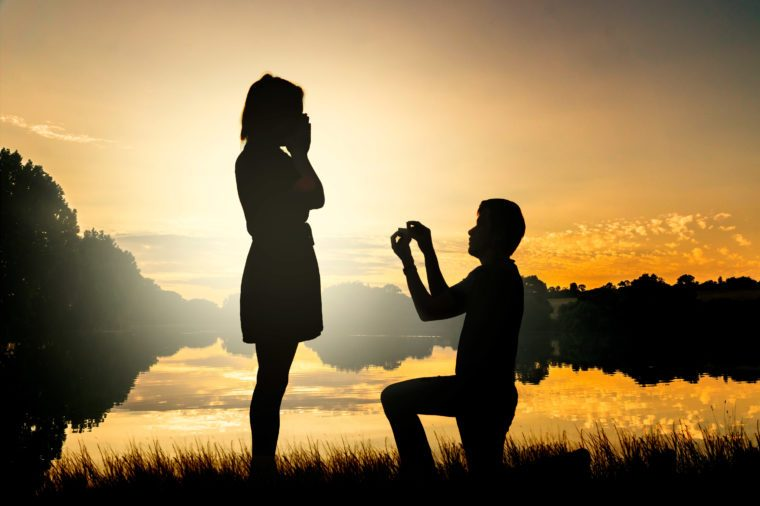 couple at a lake. wedding proposal. silhouette.