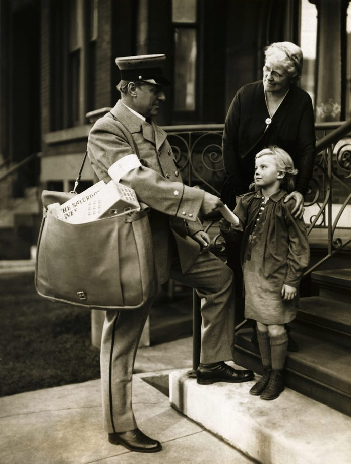 Deserting his desk in the Federal Building, Postmaster Arthur C. Leuder garbed himself in a regulation mail carrier's uniform, borrowed a mail pouch from one of his men, and personally delivered the first Christmas Sealed letter opening the 1925 campaign to raise funds to fight tuberculosis. Photograph shows Postmaster Leuder delivering the first Christmas Sealed letter to Miss Elizabeth Alexander, 6, and her grandmother Mrs. Edward P. Martin at their home at 27 Scott Street.