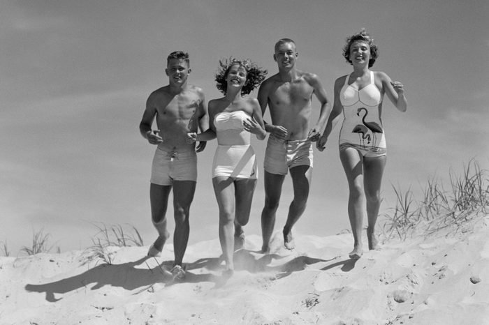 1950s TEENAGE FOURSOME TWO COUPLES IN BATHING SUITS RUNNING ON BEACH TOWARD OCEAN