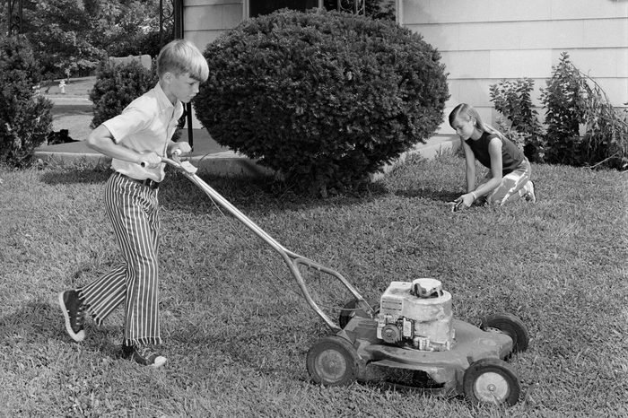 1970s BROTHER AND SISTER DOING CHORES MOWING LAWN CUTTING GRASS YARD WORK TOGETHER