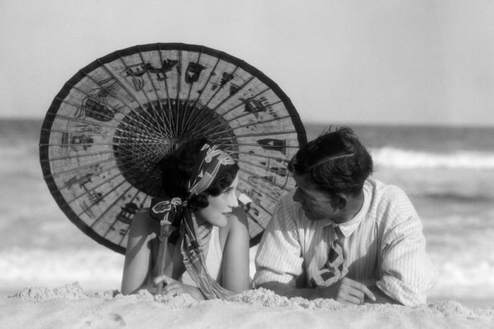 1920s ROMANTIC COUPLE MAN WOMAN LOOKING AT ONE ANOTHER LYING FACE TO FACE UNDER ORIENTAL PARASOL ON SANDY BEACH