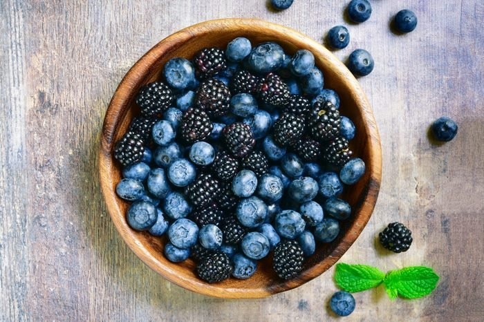 blackberries and blueberries in a bowl on wooden background