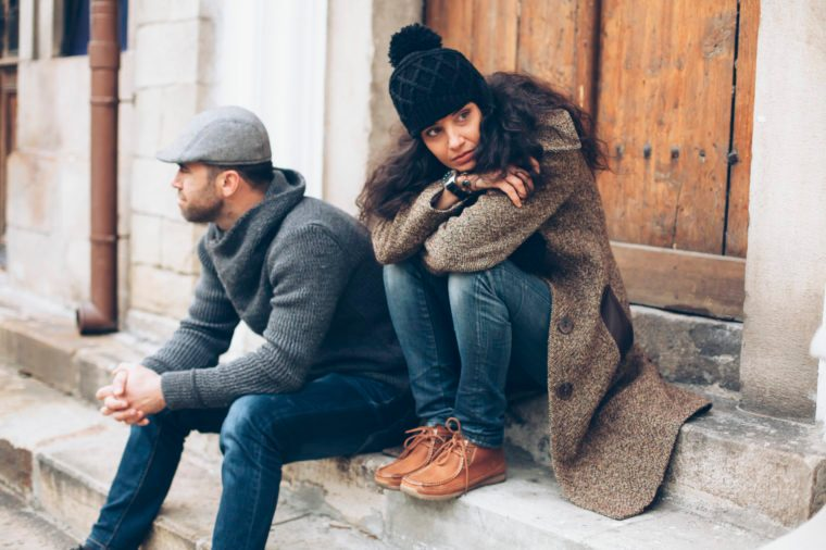 Young couple having relationship difficulties. Man and woman sitting on stairs in front of a closed wooden door. Wears warm clothes - jeans, sweater, coat, hat and scarf. Both looking in different directions. On background building facade, wooden front door, rainwater gutter and windows.