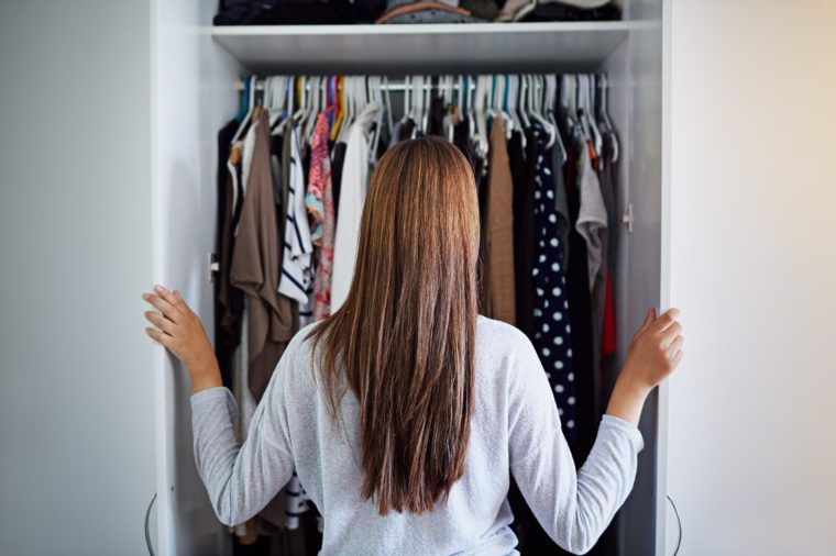 Rearview shot of a young woman standing in front of her closet choosing something to wear