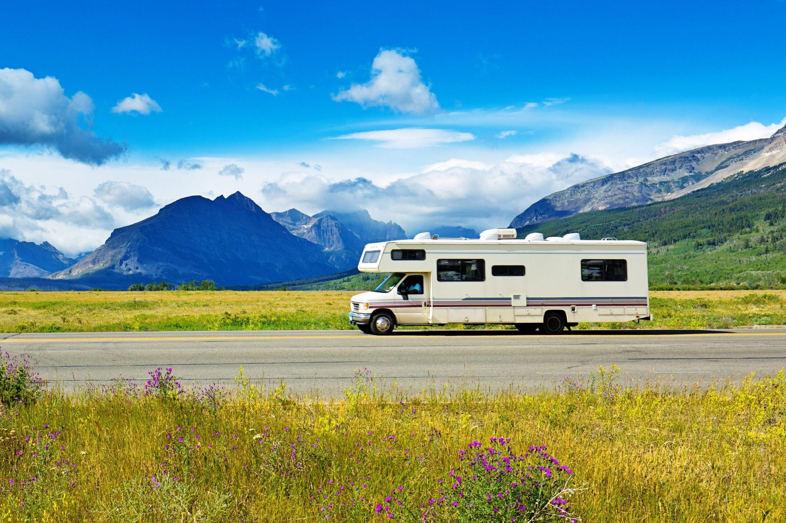 rv on the road among a beautiful landscape with mountains in the background