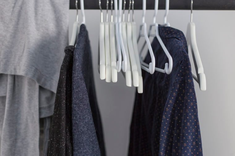 navy and black clothes hanging in a closet