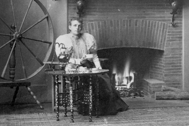 Frances Benjamin Johnston seated by the fireplace in her studio, circa 1880