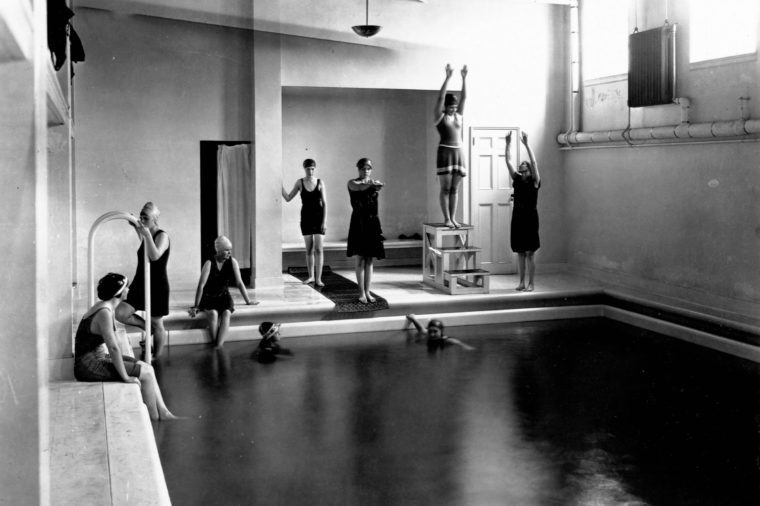 Young women sit around an indoor swimming pool at Mount Vernon Seminary. Washington, D.C., circa 1900
