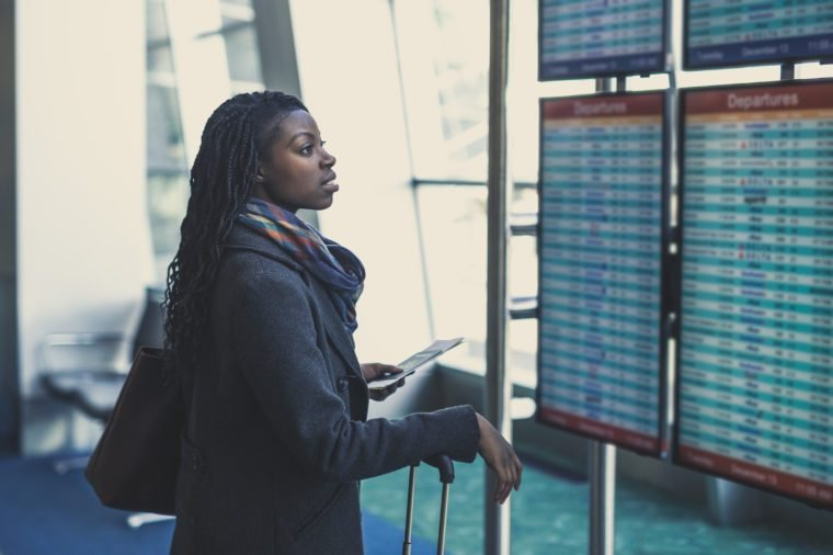 Young African American woman at airport checks the arrivals and departures board with suitcase and passport in hand
