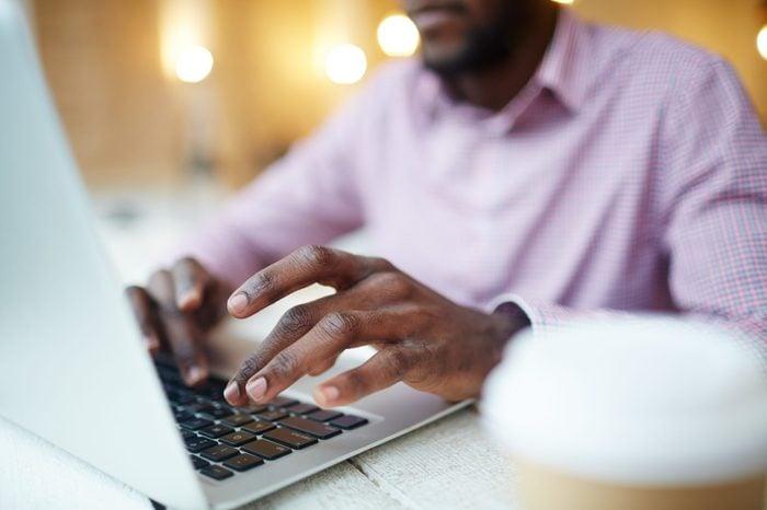 Hands of businessman or designer typing on laptop