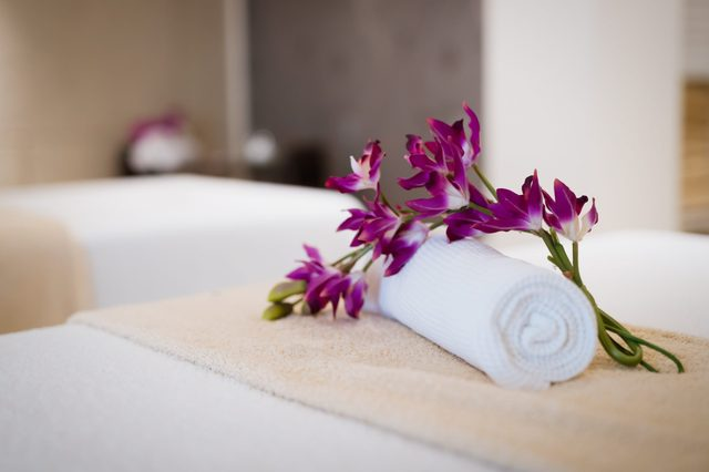 flower on a rolled towel on a massage table in a spa