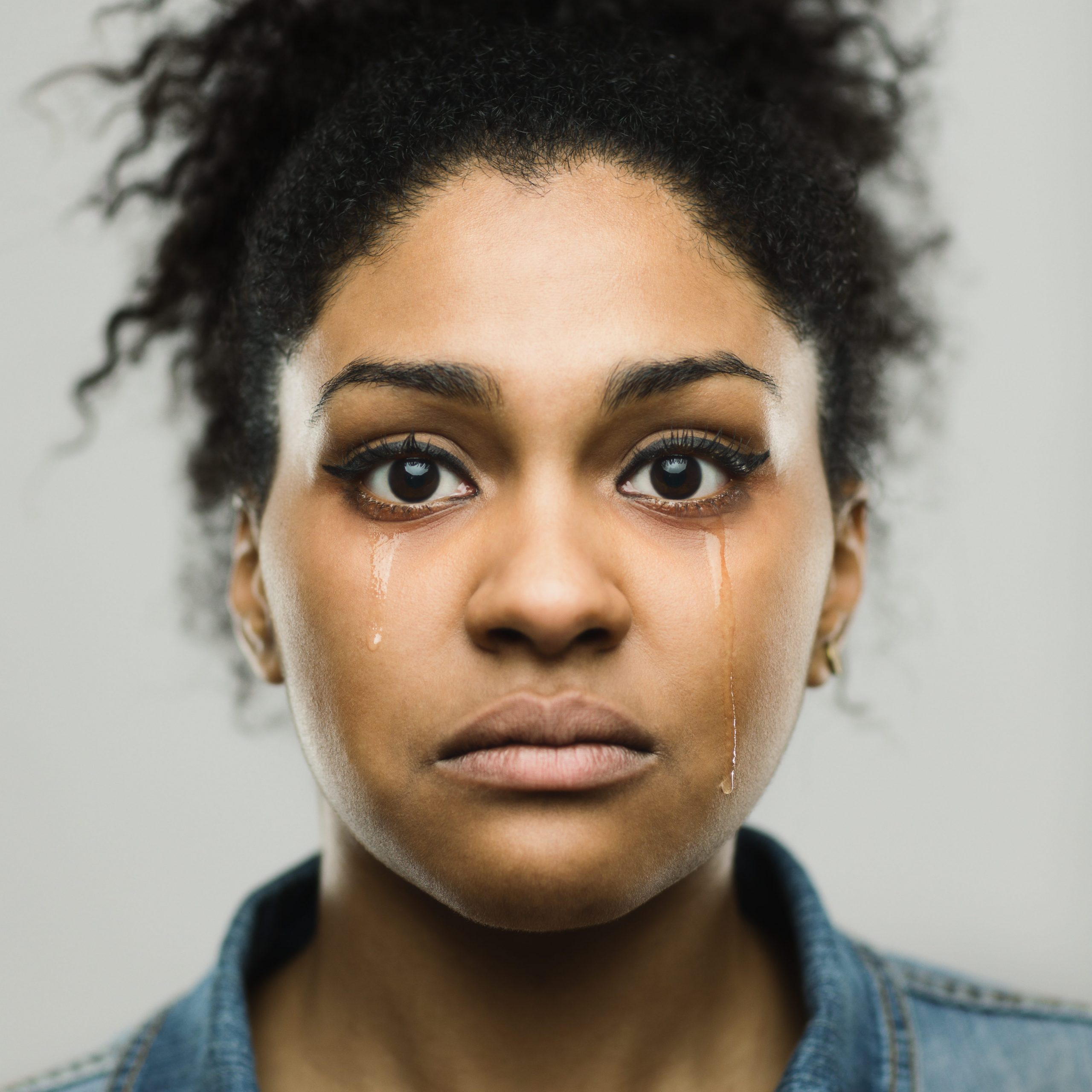 Close-up portrait of sad young afro american woman crying tears