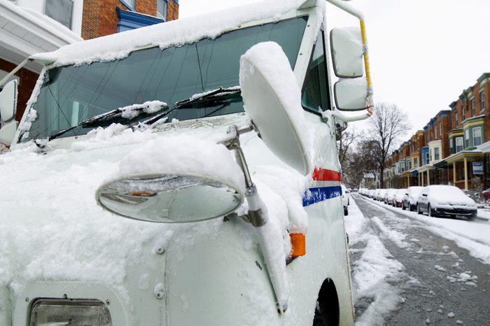 Snow Covered postal truck on a residential street in philadelphia