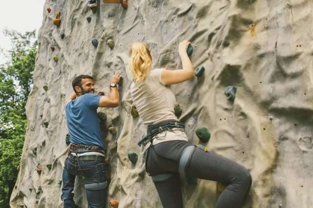 Mid adult couple on free climbing in publick park. Climbing on artificial rock wall and having fun.