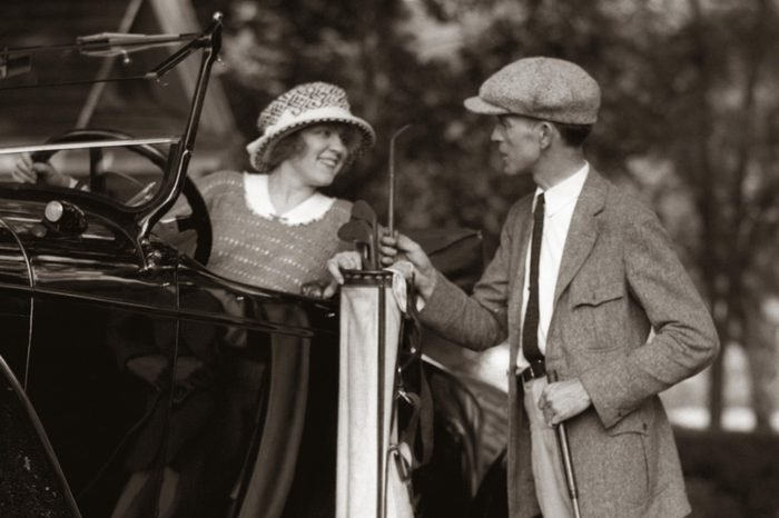 1920s COUPLE WOMAN MAN RESTING GOLF CLUBS BAG ON 1922 LINCOLN CONVERTIBLE RUNNING BOARD UPSCALE COUNTRY CLUB GOLFING LIFESTYLE