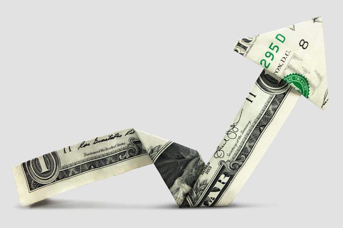 dollar bill folded like an upward trending arrow