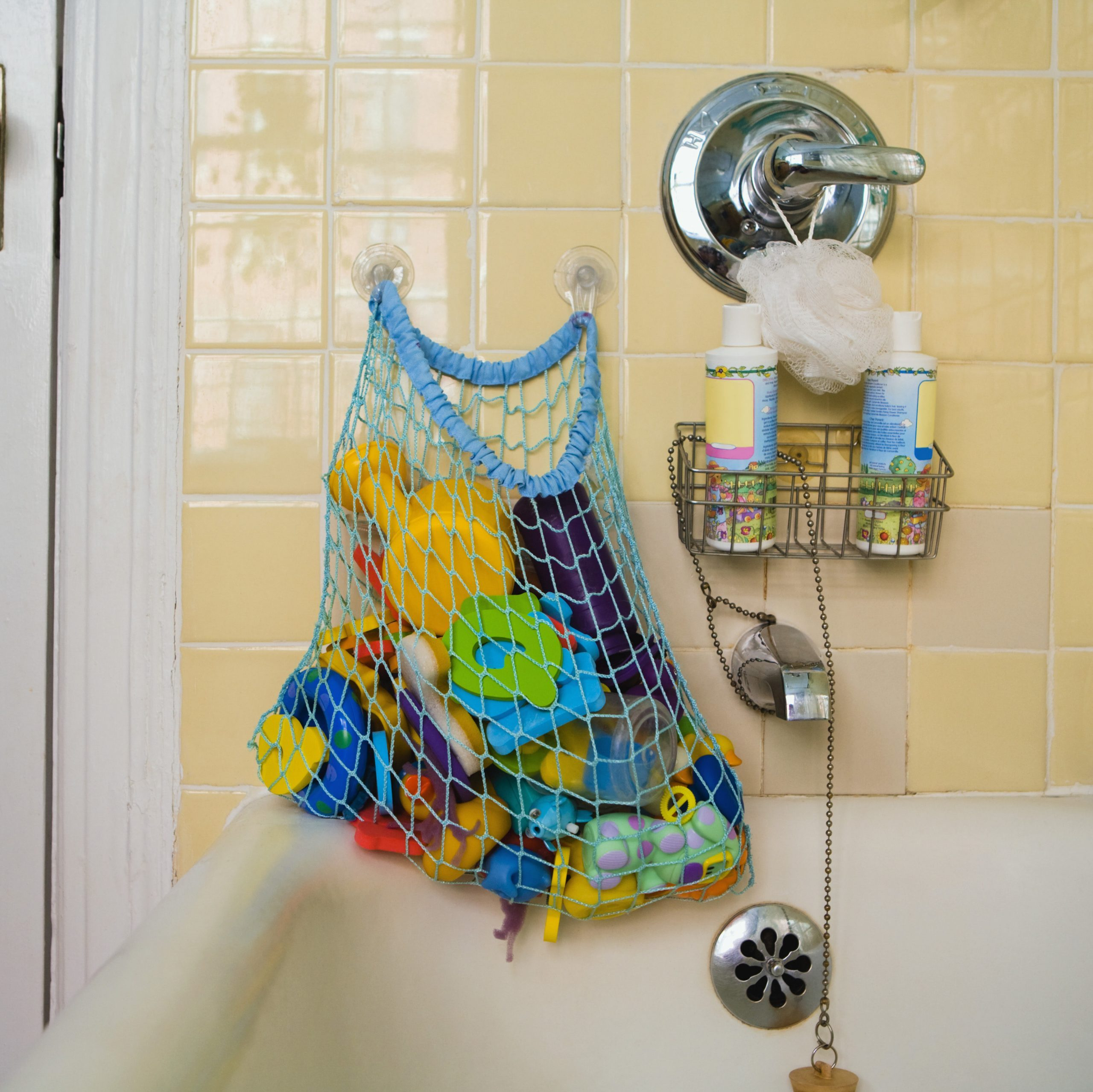mesh bag of bath toys hanging on suction cup wall hooks