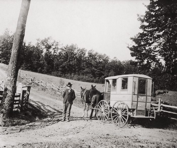 A postman resting his horses before going up a steep hill, USA, circa 1920
